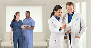 Healthcare employees wearing lab coats and scrubs