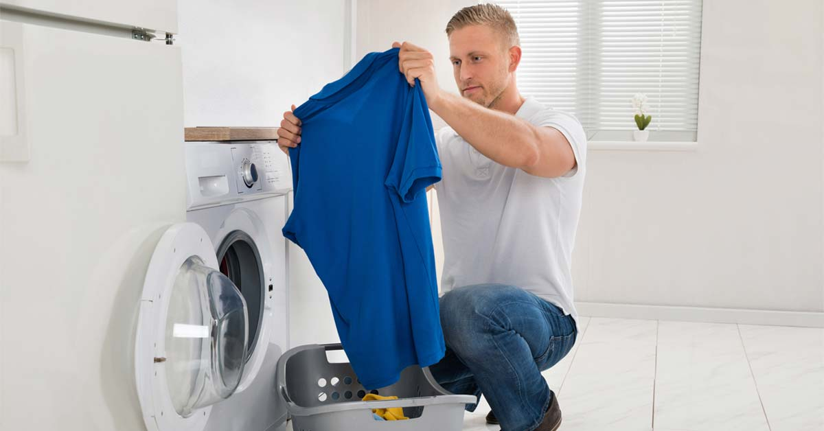 Man washing work clothing at home