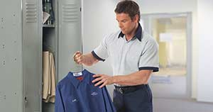 Employee holds clean, laundered, company shirt