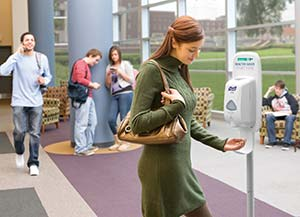 Woman disinfects hands at UniFirst purell dispenser
